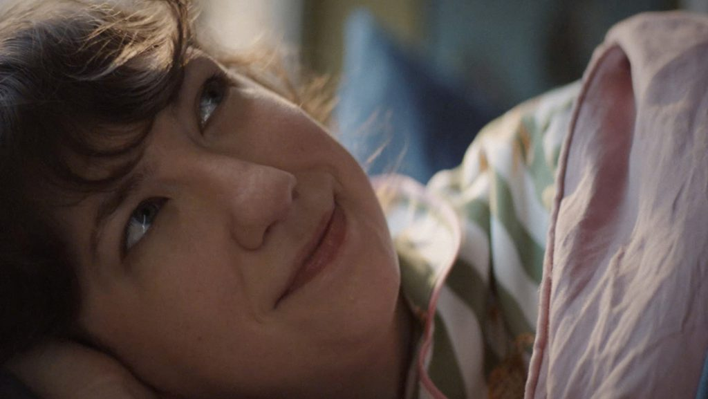 A woman wakes up in her bed in a still from Allstate's Roll Up ad