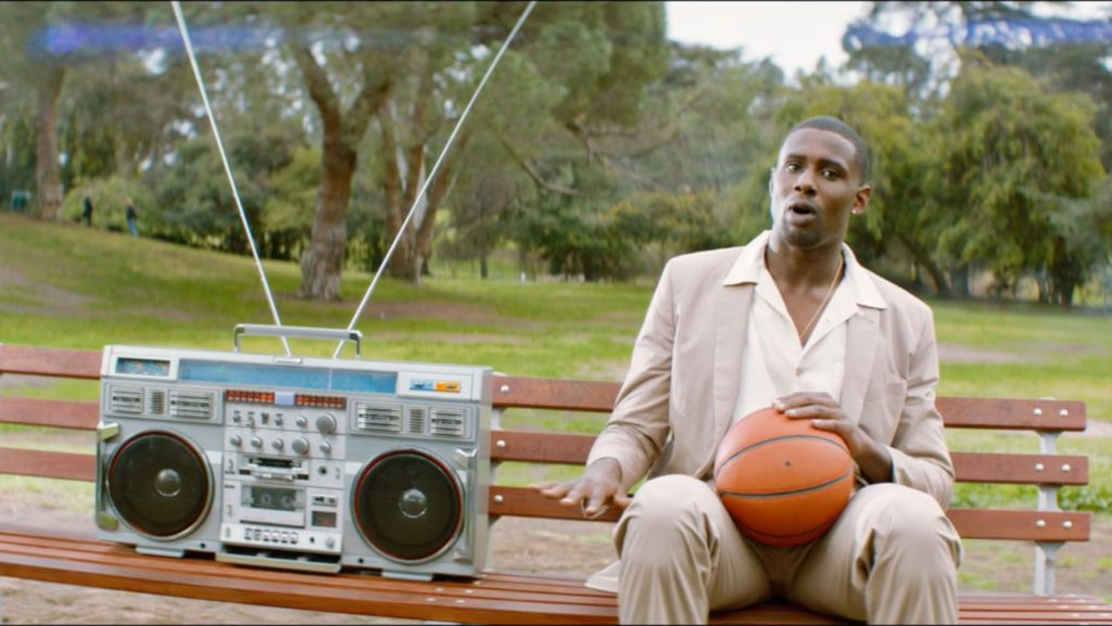 A professional basketball player sits on a bench next to a boom box in a still from ESPN's Life Needs Sports ad Smaller