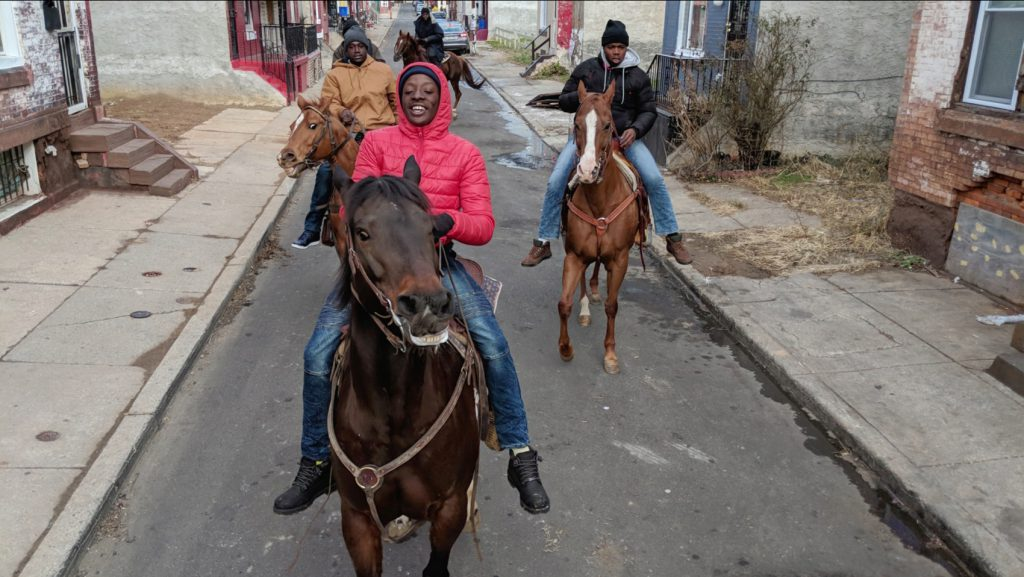 The Fletcher Street Crew rides horses through city streets in a still from the Google Pixel 2 ad showcasing them