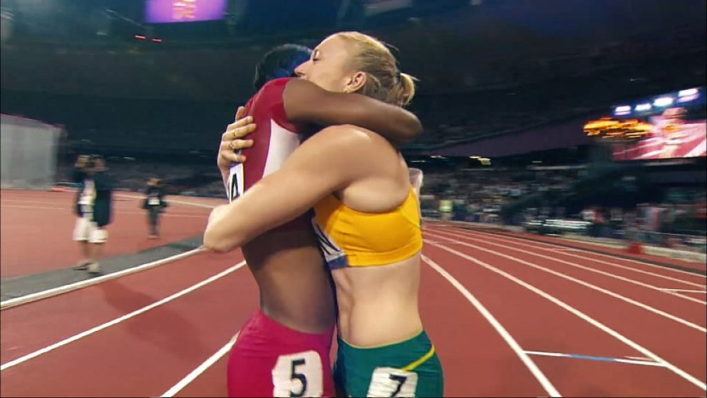 Two runners hug on the track in a still from the Olympics Together as