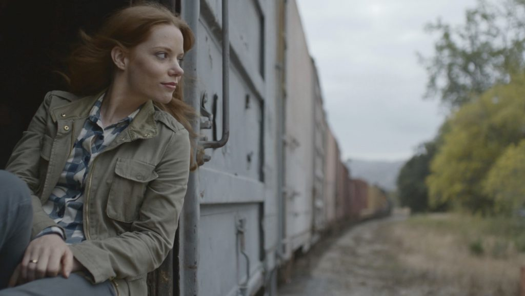 A woman rides the rails in a still from Subaru's Boxcar ad