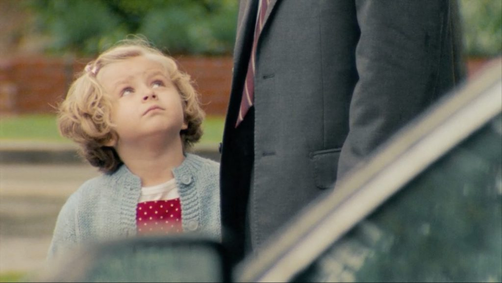 A little girl looks up at a man in a suit in a still from Subaru's Cut the Cord ad