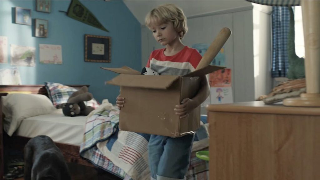 A boy carries a box of his possessions from his room in Subaru's Moving Out ad