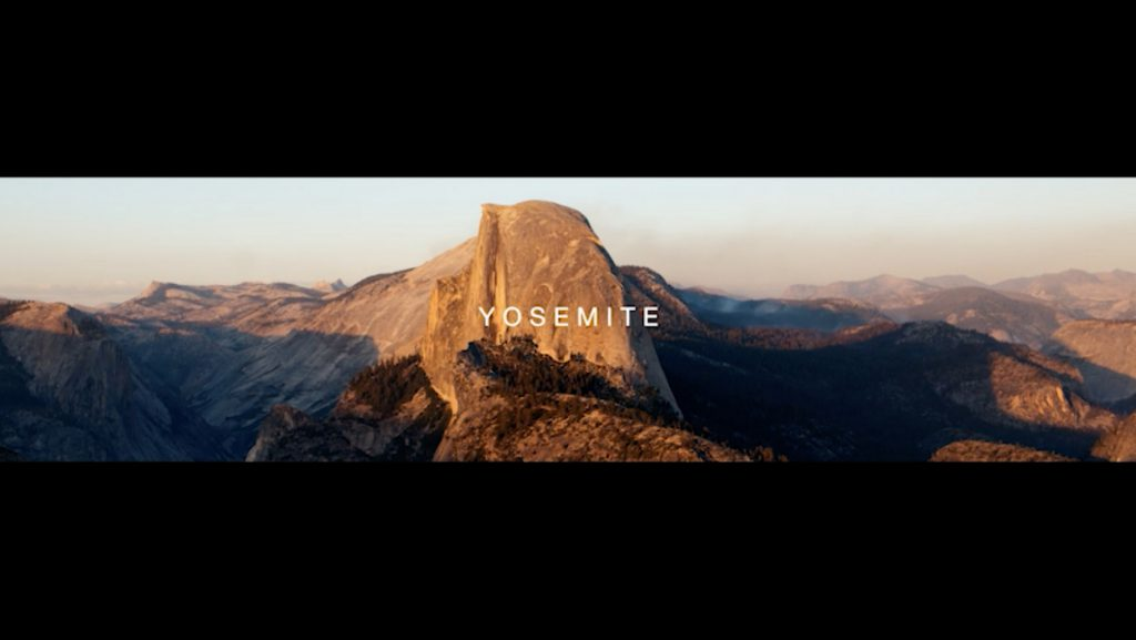 A panoramic shot of Half Dome with the word Yosemite superimposed over it in a still from Subaru's National Parks Experience video