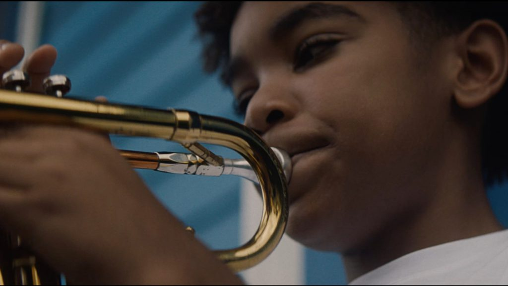 A young trumpeter plays his instrument in a still from The Trombone Shorty Foundation's Rise and Shine video